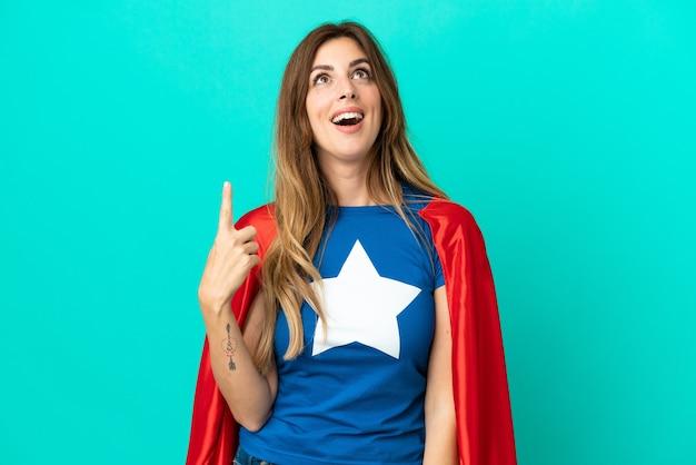 Donna caucasica super eroe isolata su sfondo blu rivolta verso l'alto e sorpresa