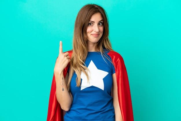 Donna caucasica super eroe isolata su sfondo blu che punta con il dito indice una grande idea