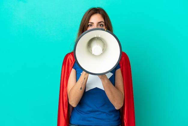 Donna caucasica del super eroe isolata sulla parete blu che grida tramite un megafono