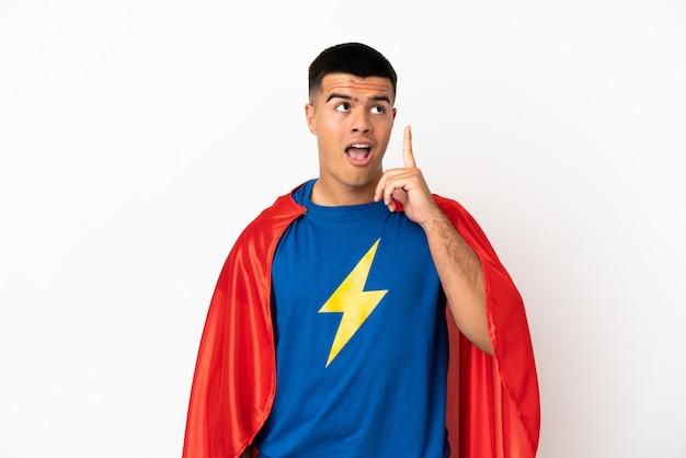 Super eroe su sfondo bianco isolato pensando a un'idea che punta il dito verso l'alto