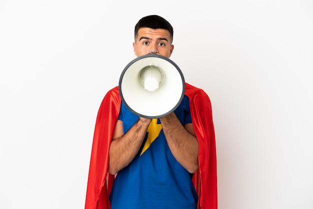 Super eroe sul muro bianco isolato che grida attraverso un megafono