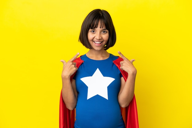 Donna incinta del super eroe isolata su fondo giallo che dà un gesto di pollice in alto