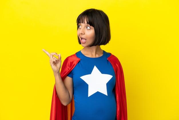 Super eroe donna incinta isolata su sfondo giallo con l'intenzione di realizzare la soluzione mentre si solleva un dito