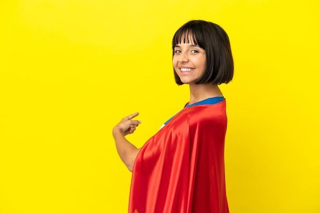 Donna incinta del super eroe isolata su fondo giallo che indica indietro
