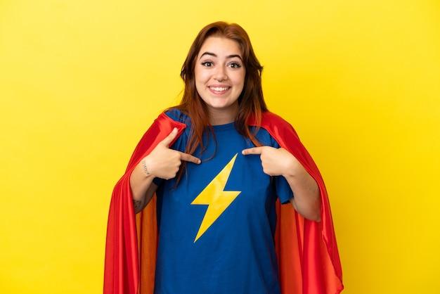 Donna rossa super eroe isolata su sfondo giallo con espressione facciale a sorpresa