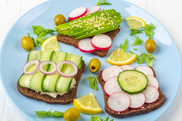 Panino vegetariano aperto di superfood con diversi condimenti: avocado, cetriolo, ravanello sul piatto blu su sfondo bianco. mangiare sano. alimenti biologici e vegetariani