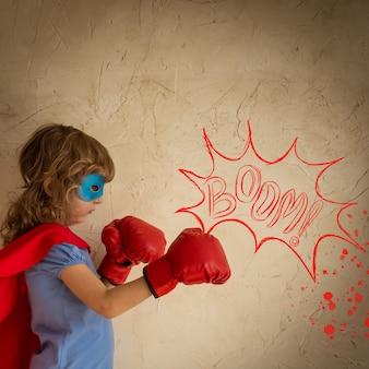 Bambino del supereroe contro il fondo del muro del grunge