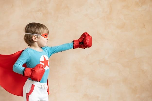 Bambino del supereroe che gioca in casa. ragazzo super eroe divertendosi al coperto. il sogno dei bambini e il concetto di immaginazione