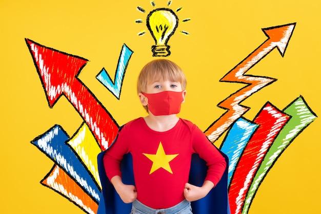 Bambino del supereroe che gioca al coperto
