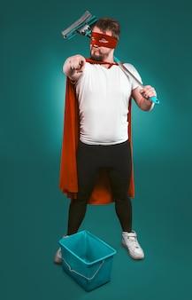 Il supereroe è pronto a lottare per la pulizia, l'uomo coraggioso in un'uniforme rossa da supereroe con un secchio e una scopa punta la telecamera con il dito indice.