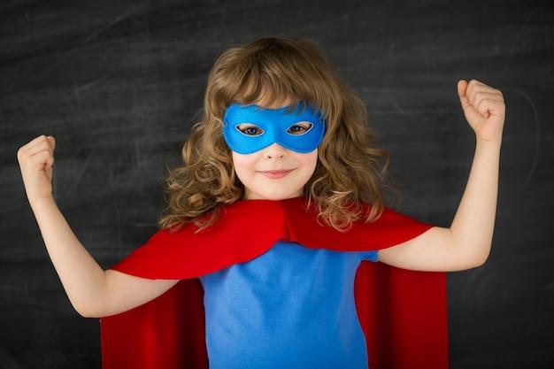 Ragazzo supereroe contro la lavagna della scuola
