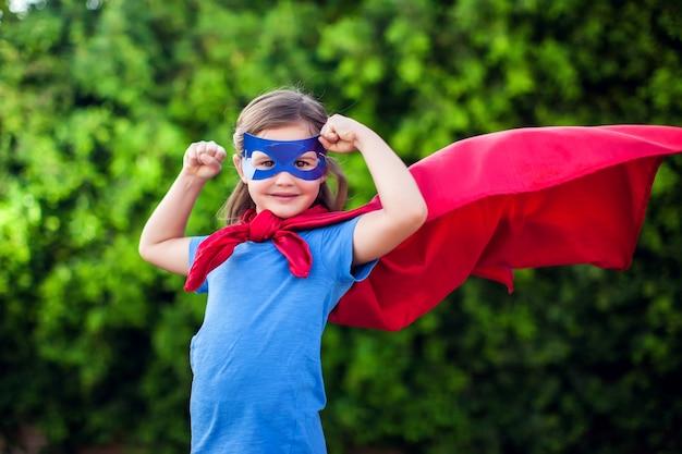 Ragazza del bambino del supereroe contro all'aperto verde