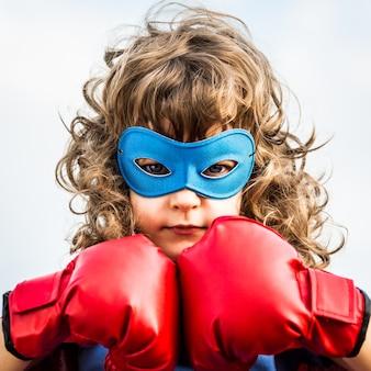 Bambino del supereroe che indossa i guantoni da pugile contro il fondo del cielo blu. girl power e concetto di femminismo