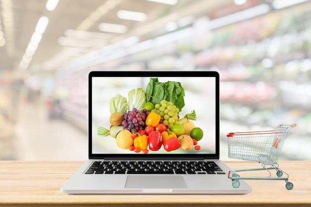 La navata del supermercato ha offuscato il fondo con il computer portatile e il carrello della spesa sul concetto online della drogheria della tavola di legno