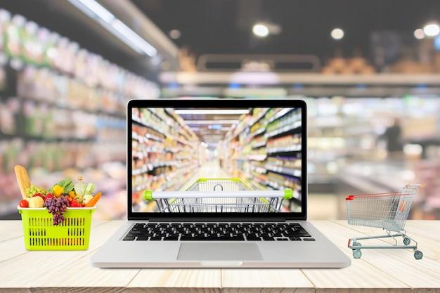 La navata del supermercato ha offuscato lo sfondo con il computer portatile e il carrello della spesa sul concetto online della drogheria della tavola di legno