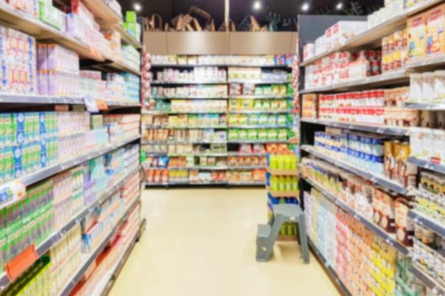 Sfocatura dell'obiettivo del corridoio del supermercato con il prodotto della scatola del latte sugli scaffali