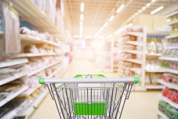 Gli scaffali dei prodotti del corridoio del supermercato interni sfocano lo sfondo con il carrello della spesa vuoto