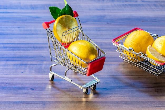Cestino del supermercato e carrello del supermercato che trasportano foglia verde e limone