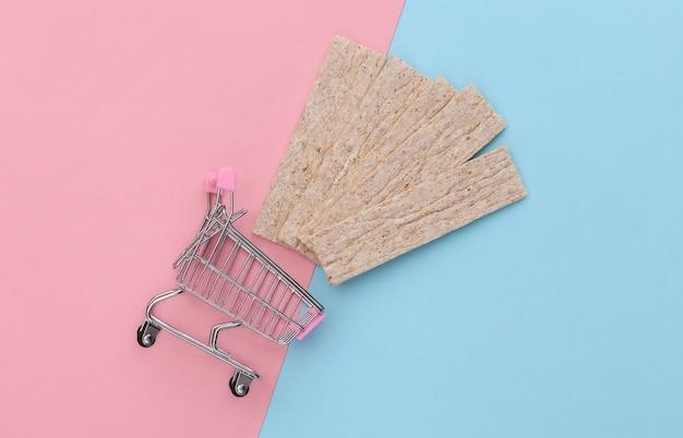 Carrello del supermercato con pane croccante di dieta su fondo pastello rosa blu.