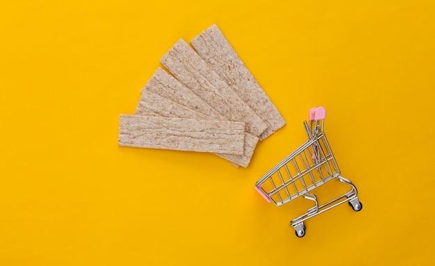 Carrello del supermercato con pane croccante di dieta su cenni storici gialli.