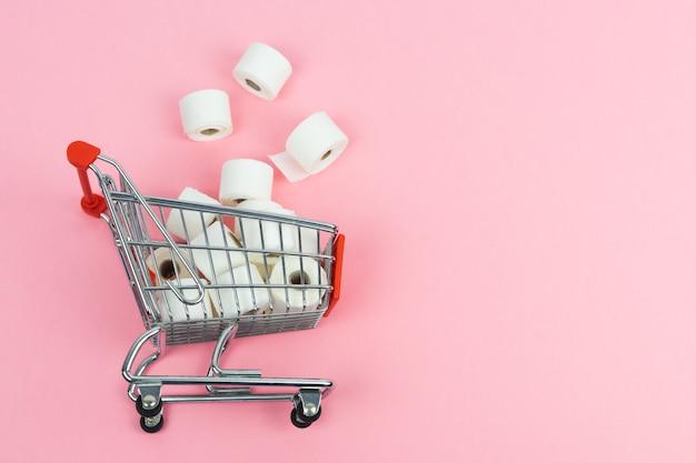 Carrello del supermercato con la carta igienica gettata sul pavimento. concetto covid-19. copia spazio.