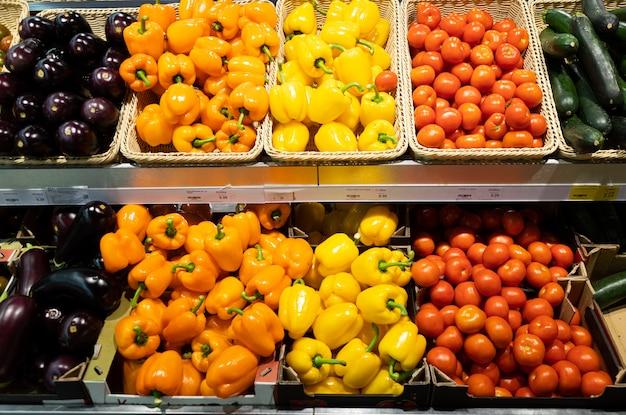 Bancone del supermercato con cestini di vimini e scatole di cartone con pomodori, zucche, peperoni e melanzane arancioni e gialli