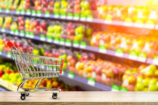 Fondo del tavolo della drogheria del supermercato con il cibo del carrello e generi alimentari sfocati sugli scaffali dei negozi