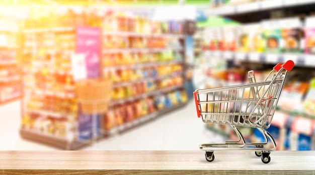 Fondo del tavolo della drogheria del supermercato con il cibo del carrello e generi alimentari sfocati sugli scaffali dei negozi di alta qualità...