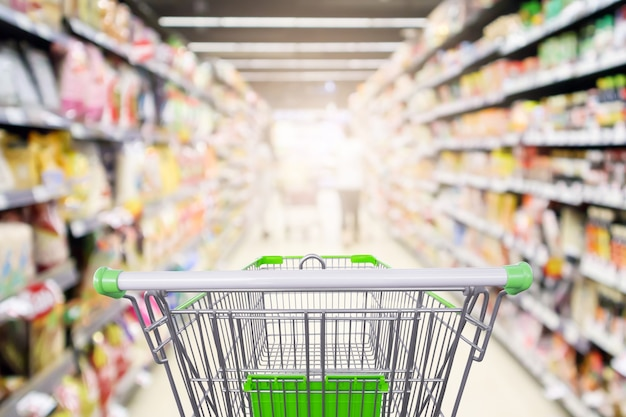 La navata laterale degli scaffali del supermercato con il carrello della spesa vuoto ha sfocato lo sfondo della luce del bokeh sfocato interno