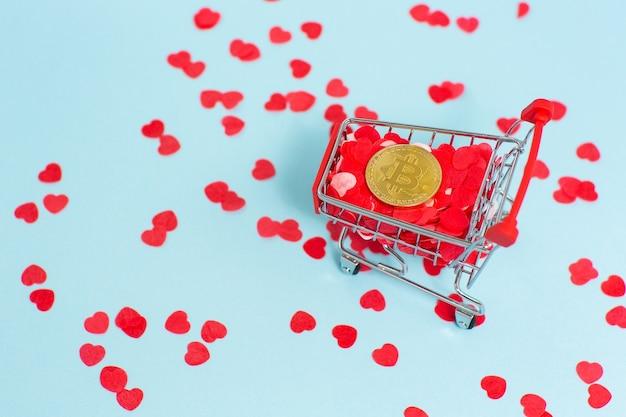 Il carrello del supermercato è pieno di cuori rossi e un bitcoin dorato