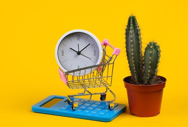 Carrello del supermercato con orologio, calcolatrice e cactus su colore giallo