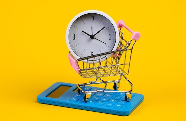 Carrello del supermercato con orologio, calcolatrice su giallo
