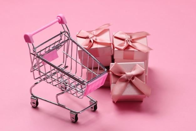 Carrello del supermercato con scatole regalo su pastello rosa