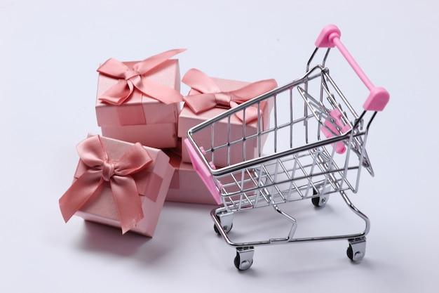 Carrello del supermercato con scatole regalo su un bianco