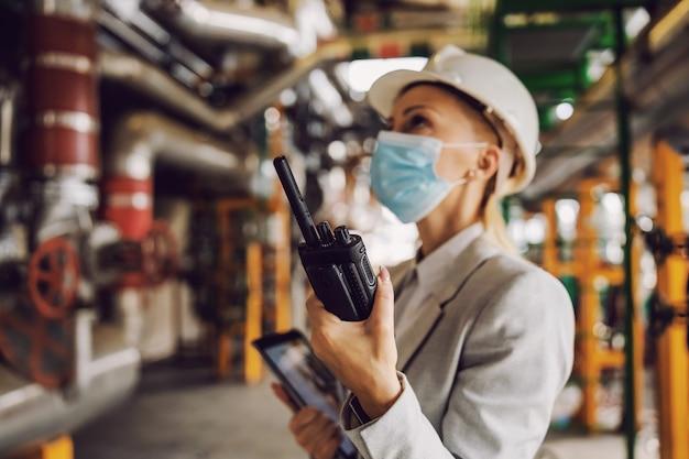 Supervisore che tiene il tablet e parla al walkie-talkie nell'impianto di riscaldamento durante il coronavirus.