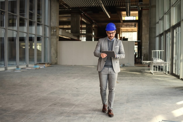 Supervisore che cammina nell'edificio nel processo di costruzione con il tablet in mano e controlla i lavori