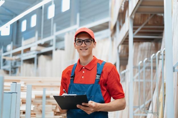 Il supervisore con un blocco per appunti si trova in un magazzino con un pannello laminato