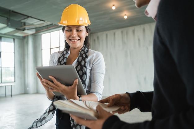 Ingegnere della donna del supervisore che guarda una progettazione della proprietà sulla compressa digitale