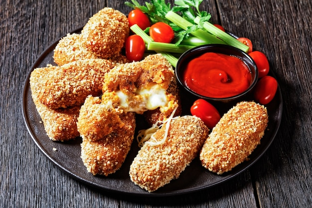 Suppli al telefono fast food italiano - crocchette di riso fritto ripiene di mozzarella servite su un piatto nero con gambi di sedano, pomodori e ketchup su un tavolo di legno scuro, vista dall'alto, primo piano