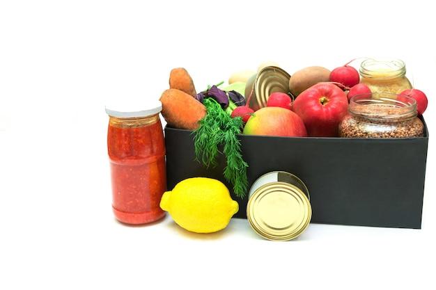 Fornisce una scatola di aiuti alimentari piena di verdure, conserve, cereali, uova e frutta. casella di donazione per la consegna di beneficenza con copia spazio.