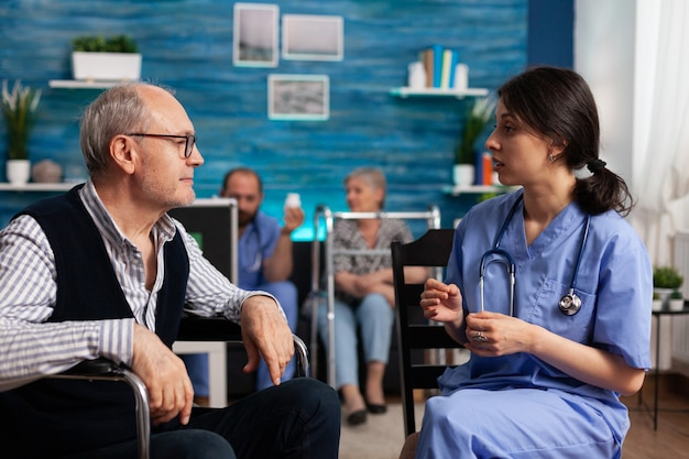 Sostenere l'assistente che spiega il trattamento sanitario a un uomo anziano disabile