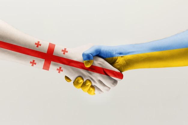 Gesto di supporto due mani che si stringono colorate nella bandiera dell'unità europea e dell'ucraina isolate