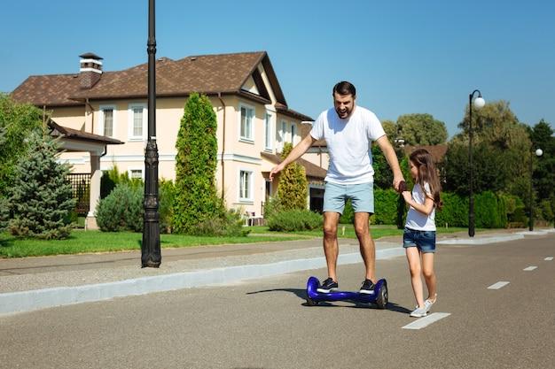 Ti sostengo. bambina sveglia che tiene la mano del suo amato padre cavalcando un hoverboard lungo la strada e fornendo supporto a lui