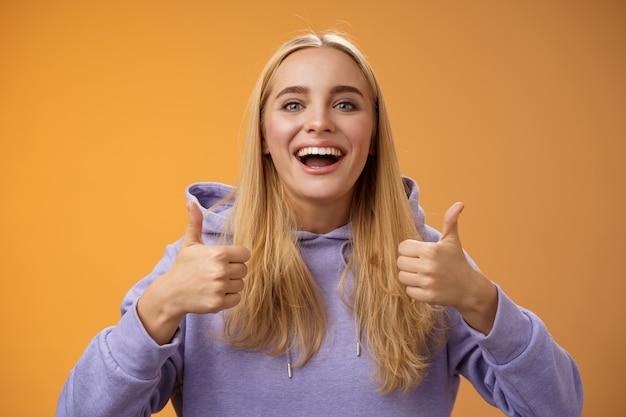 Fidanzata bionda carina solidale che esulta simpatia concetto interessante idea cool pollice in su sorridente ampiamente d'accordo approva outfit shopping insieme amici, consiglia adoro nuovo look, sfondo arancione.