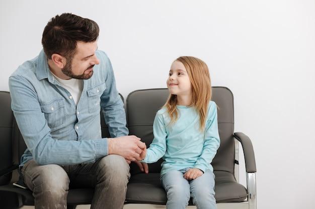 Papà solidale e il suo grazioso bambino seduto sulle sedie con suo figlio prima di fare una visita dal medico