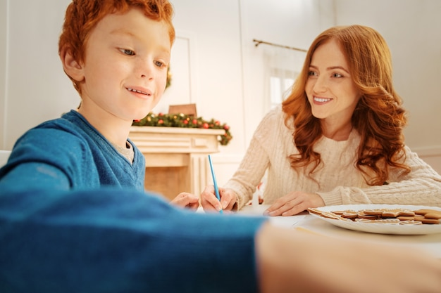 Relazioni di supporto. bambino rosso gioioso che sorride seduto accanto alla sua mamma allegra e si gode una chiacchierata in famiglia con lei.