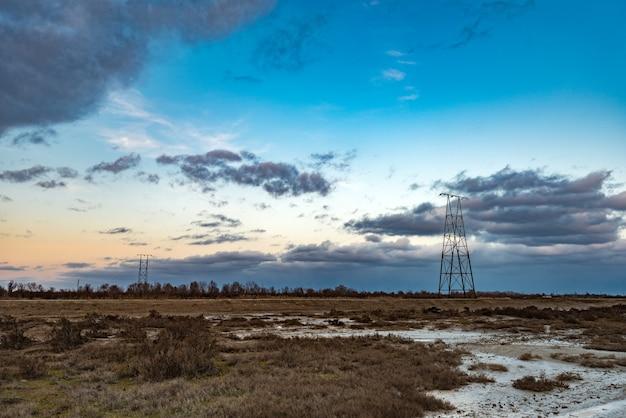 Supporti di linee elettriche ad alta tensione su contro il bel cielo