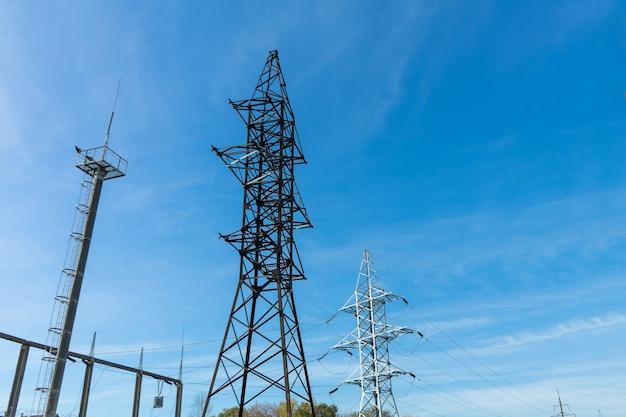 Supporta linee elettriche ad alta tensione contro il cielo azzurro con nuvole. industria elettrica.