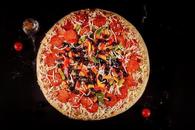 Pizza suprema con olive, olio, pomodorini su nero.