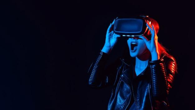 Ragazza sorpresa che indossa occhiali per realtà virtuale con luci rosse e blu